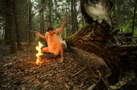 Primitive man makes fire in forest