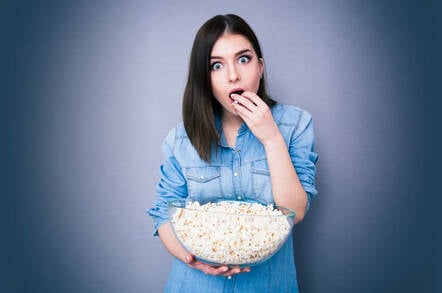 A woman eating popcorn in shock