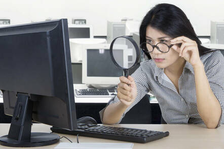 Woman peering at something in her office using a magnifying glass