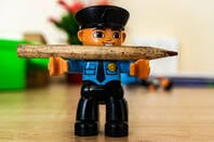 Figurine of a policeman with a  pencil