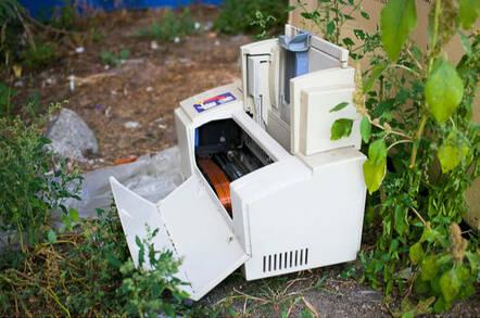 ewaste: a broken printer lies abandoned in an alleyway, weeds growing through it.