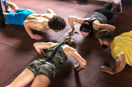 People doing push-ups in a gym
