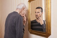 Older man looking at younger self in the mirror