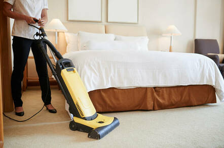 Maid cleaning carpet in hotel room