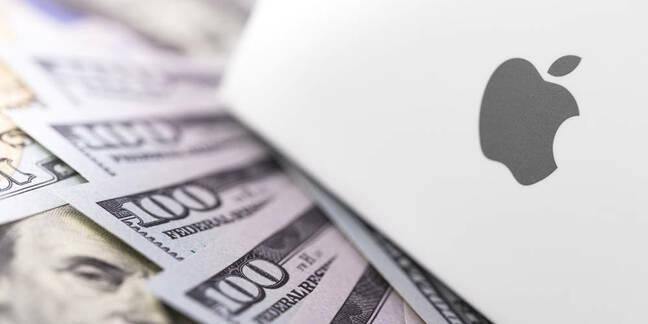 An Apple laptop next to $100 bills