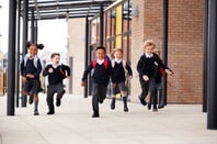 schoolchildren run outside to their parents