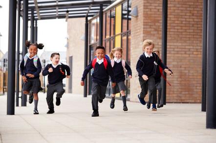 schoolchildren run outside to their parents
