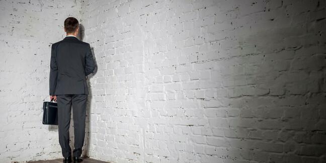 Businessman stands in a corner
