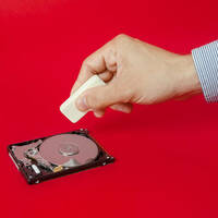 A hand taking an eraser to a hard drive