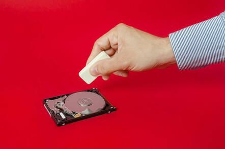 A hand taking an eraser to a hard drive