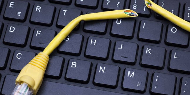 A cut-up ethernet cable sits on a keyboard