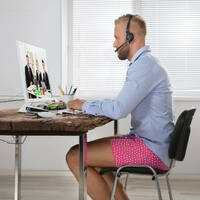 Someone working from home in a shirt and underwear on a video conference call