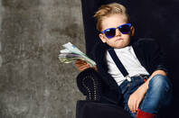 A kid holding a wad of cash