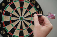 A person's hand tossing a dart