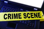 Computer with a police crime scene banner over it
