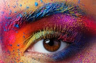 A human eye surrounded by colorful face paint