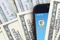 Chrome on a mobile phone amid $100 bills