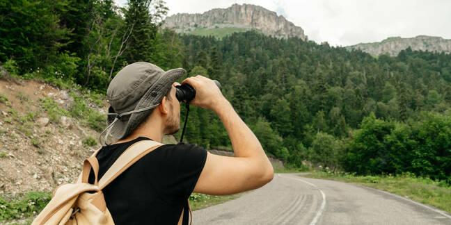 hiker looks through binoculars at nature