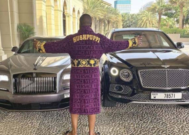Hushpuppi standing in front of some expensive cars