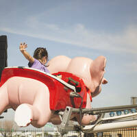 Girl on elephant fairground ride waves goodbye