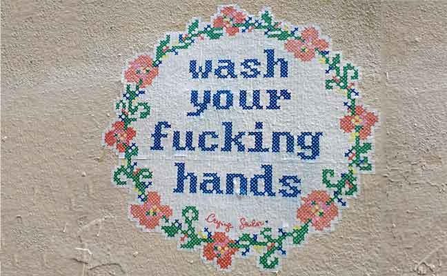Street graffiti that says wash your fucking hands