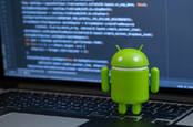 Google Android toy in front of a laptop showing some code