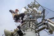 A technician climbing a cellphone tower