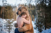 A guy hugging a bear. Presumably in Russia