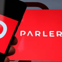 Someone holding a phone showing the Parler logo