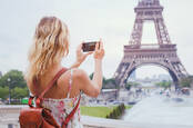 Someone taking a photo of the Eiffel Tower using their smartphone