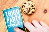 A phone showing 'third party cookies?' on screen next to a cookie