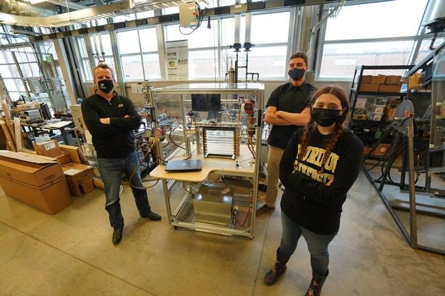 Test de l'inondation de liquide dans l'expérience du réfrigérateur.  Les chercheurs de Purdue Eckhard Groll (à gauche), Leon Brendel et Paige Beck se tiennent à côté de l'expérience