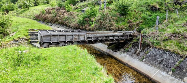 This wooden gutter carries water from a mountain stream over one on the leats