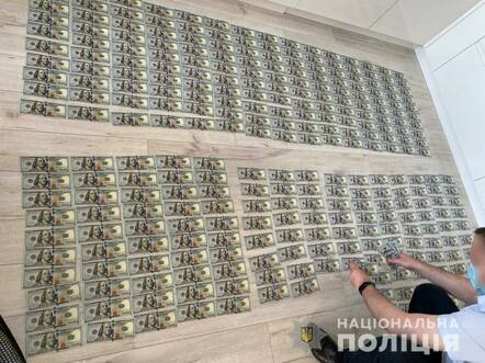 Handout from Ukrainian Police boasting of seized cash from Clop ransomware gang
