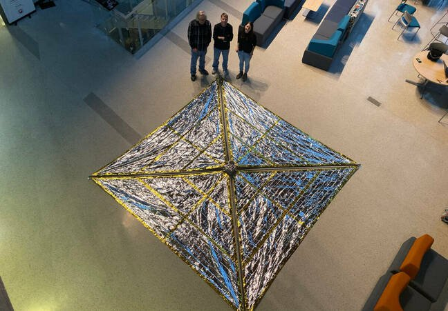 Drone view of the Spinnaker3 drag sail prototype, fully deploying in the atrium of the Neil Armstrong Hall of Engineering at Purdue University. Pictured from left to right: Anthony Cofer, David Spencer, Arly Black
